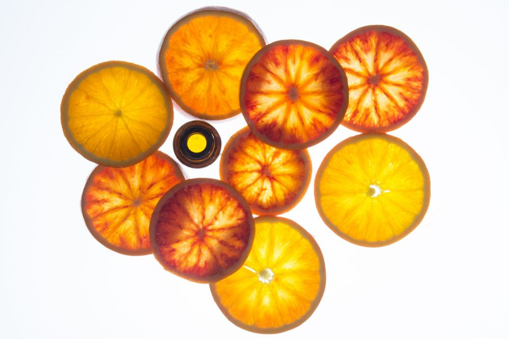 Essential oil bottle with blood orange slices with backlight